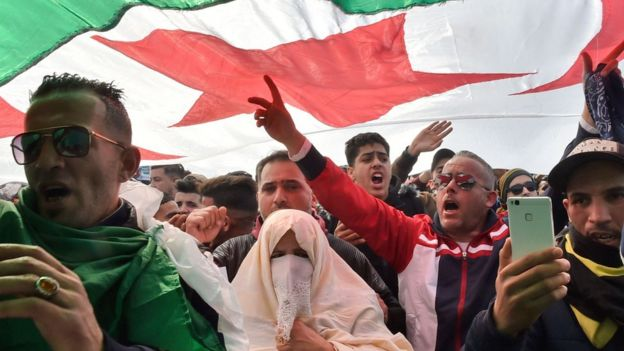 Algerians chant slogans under a national flag during a protest rally against ailing President Bouteflika's bid for a fifth term in power, in the capital Algiers on 1 March 2019