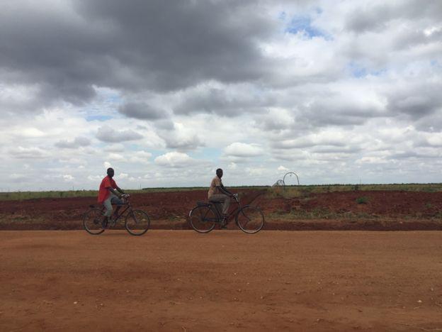 Garotos andam de bike em frente a um campo