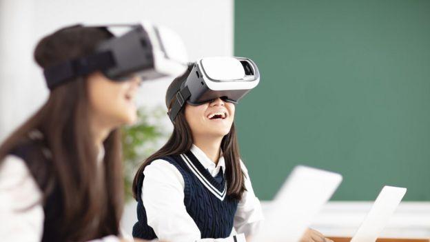 Estudante usa óculos de realidade virtual enquanto sorri