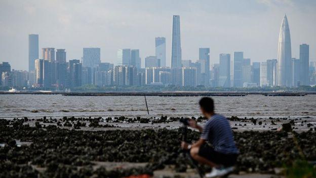 一名男子在香港隔海拍摄深圳天际线。