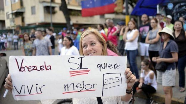 Mujer con un cartel a favor de la consulta