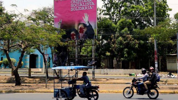 Un letrero semi destruido con los rostros de Daniel Ortega y Rosario Murillo