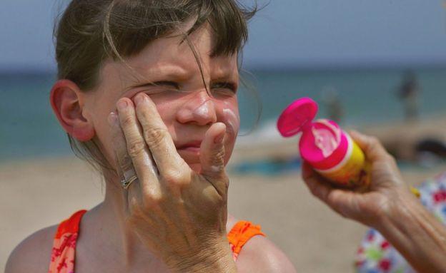 Mujer da crema en la playa a una niña.