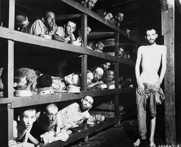 Trabalhadores escravizados em seus leitos no campo de concentração após a libertação em abril de 1945. Nesta foto, está Elie Wiesel, futuro vencedor do Nobel da Paz, sétimo a partir esquerda, na segunda fileira de beliches, junto à viga de madeira