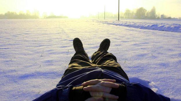 Pessoa admira paisagem deitada na neve