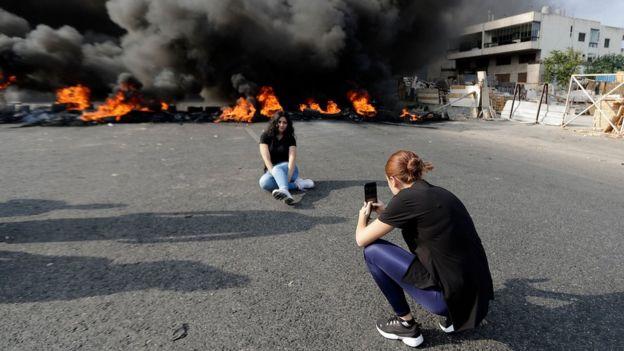 من أكثر الصور المتداولة على مواقع التواصل الإجتماعي صورة هذه المرأة تأخذ لصديقتها صورة لها أمام اكوام الإطارات المطاطية المحروقة في لبنان الجمعة 18 أكتوبر تشرين الأول