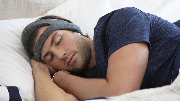 Homem dormindo com faixa de cabeça que auxilia no sono