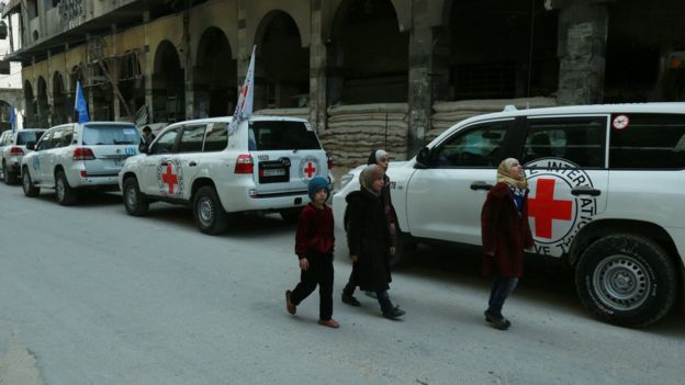 Syrian children walk past vehicles of the UN and the International Committee of the Red Cross (ICRC) delivering humanitarian aid in the Syrian town of Douma
