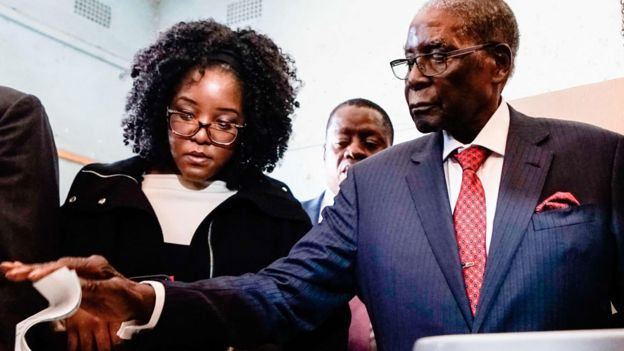 Bona Mugabe (L) helping her father Robert Mugabe to vote in Zimbabwe - Monday 30 July 2018