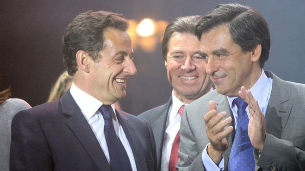 Nicolas Sarkozy, left, laughs on stage alongside Francois Fillon
