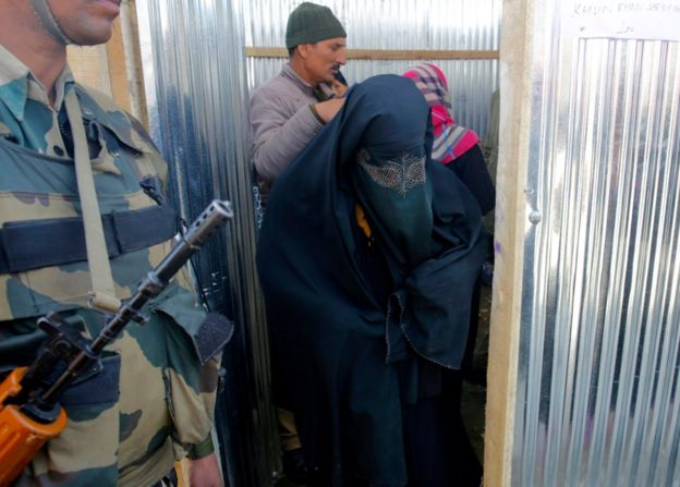 A Kashmiri Muslim woman walks past a paramilitary solider after casting her vote during parliamentary by-elections in Srinagar, the summer capital of Indian Kashmir, 9 April 2017.