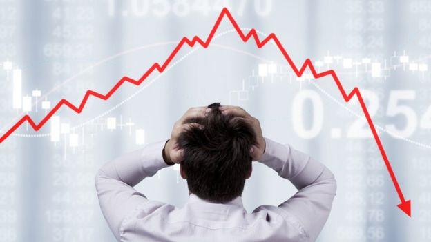 Hombre frente a gráfico mostrando una caída de valores.