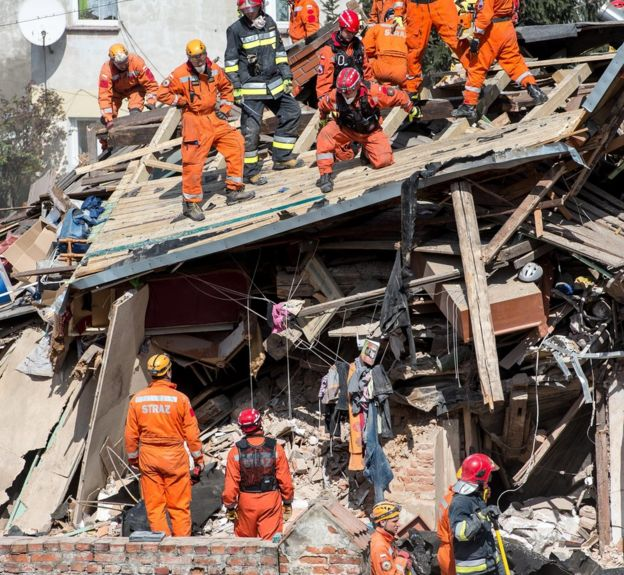 Polish rescue workers at the scene of the building collapse