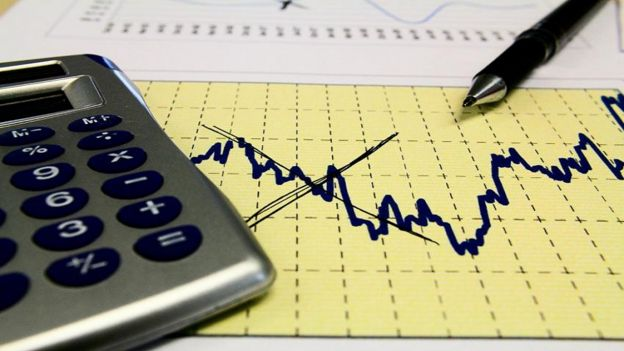 Calculadora e caneta ao lado de papel exibindo gráfico
