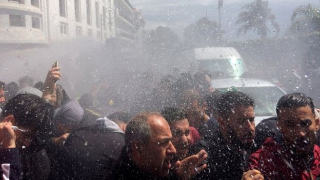 Crowds are seen being wet by police