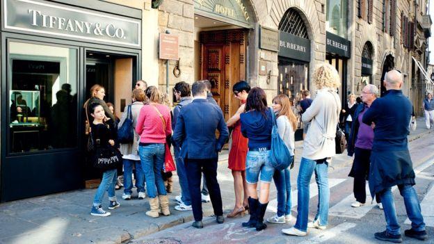 Un grupo de gente hace fila a la entrada de una tienda.