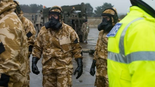 Military personnel pictured in gas masks at Winterbourne Gunner before deployment to Salisbury