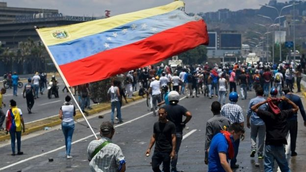 An opposition demonstrator holds a large Venezuelan flag amid a large scattered crowd