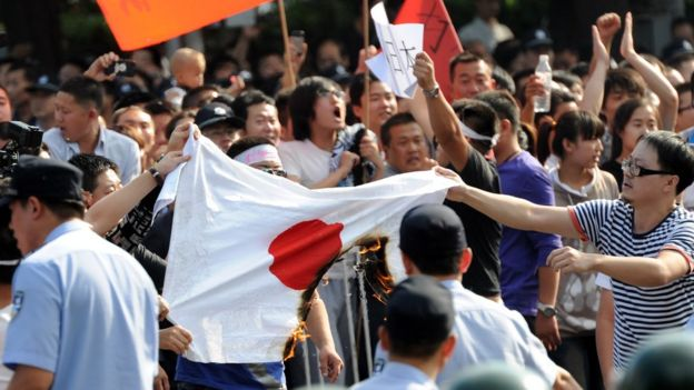 Chinese protesters burn a Japanese national flag during an anti-Japanese protest over the Diaoyu islands issue, known as the Senkaku islands in Japanese, outside the Japanese Embassy in Beijing on September 15, 2012