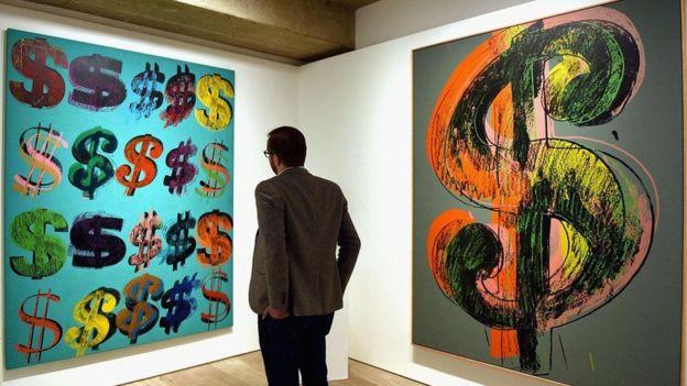 Homem observa obras de Andy Warhol com símbolos do cifrão