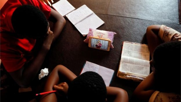 Teenagers watch the live broadcast of church service from home as all religious gatherings are suspended over concerns of the spread of coronavirus disease (COVID-19), in Accra, Ghana, March 22, 2020.