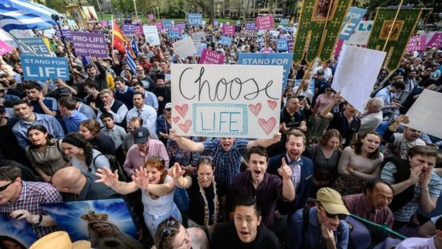 "A group of pro-life supporters hold placards including ""choose life"""