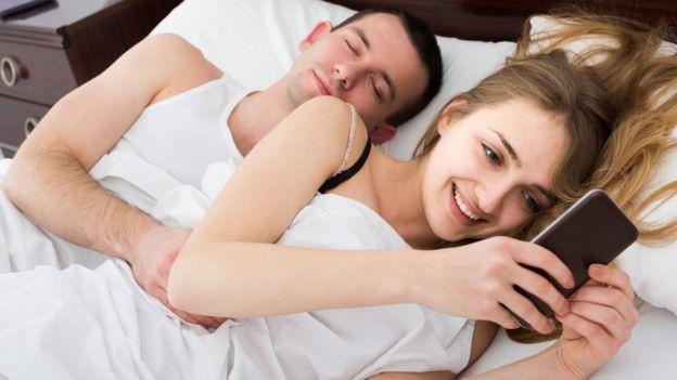 Una pareja descansa mientras la mujer mira el teléfono sonriente.