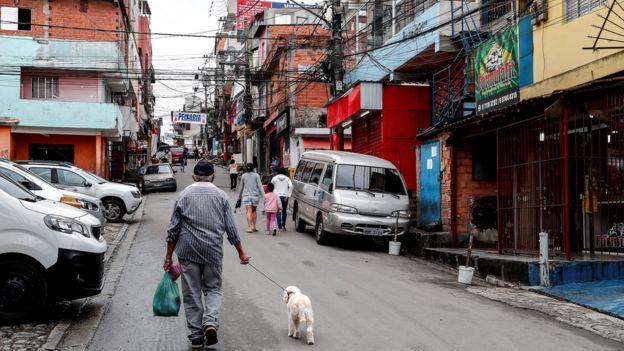 Moradores caminhando em rua de Paraisópolis