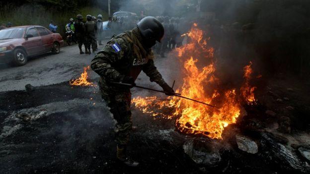 Un soldado extingue un fuego en Tegucigalpa.