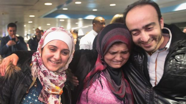 An immigrant family is at an airport in the United States.