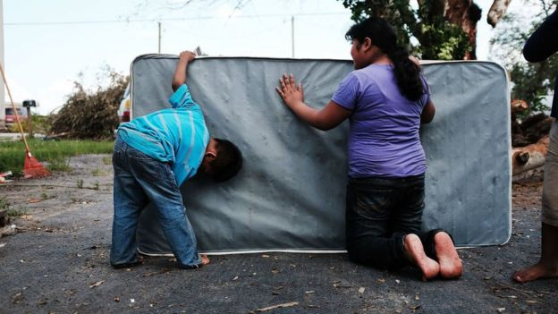 Two children clean a mattress that got dirty by the floods.