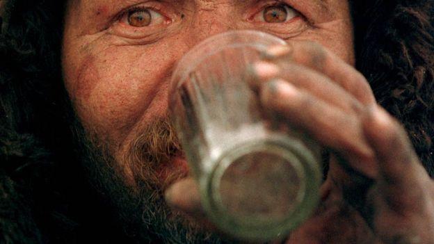 Мужчина пьет водку из граненого стакана