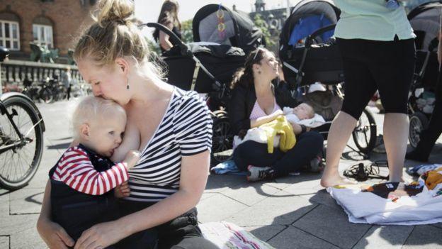 Madre amamantando a su bebé en una plaza.