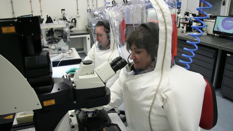 Ученые в защитных костюмах
