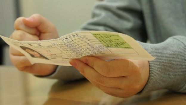 Jin-yeong sostiene la vieja tarjeta de asistencia al examen