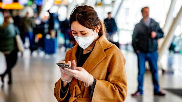Una mujer con tapabocas y guantes sostiene un teléfono en un aeropuerto.