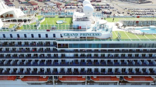 Passengers look out as the Grand Princess cruise ship docks at the Port of Oakland in Oakland, California on 9 March, 2020