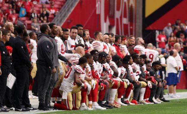 Jugadores sentados y arrodillados durante el himno.