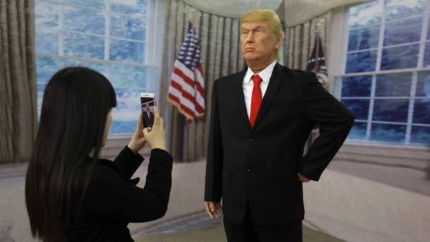 A Chinese visitor taking a photo of a wax figure of US President Donald Trump in Shenyang, northeastern China's Liaoning province