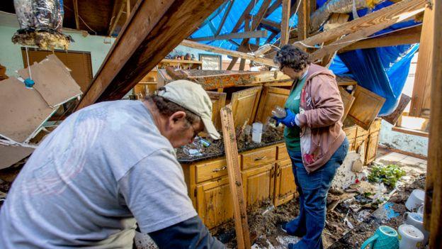 Una pareja examina los restos destrozados de la cocina de su casa en Longs, Florida