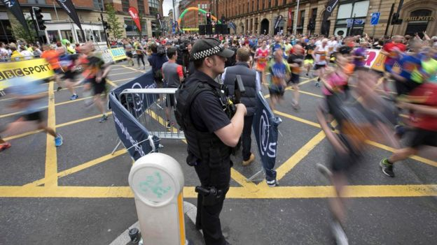 An armed police officer oversees the race