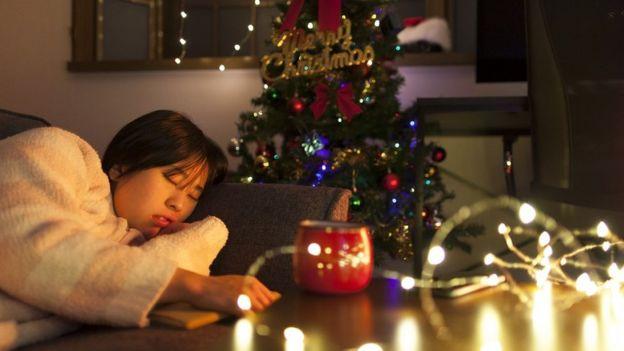 девушка спит у новогодней елки