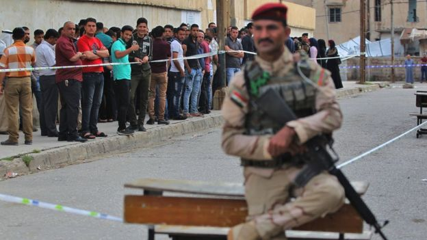 Members of the Iraqi security forces stand guard as people queue at a polling station in Mosul, 12 May 2018
