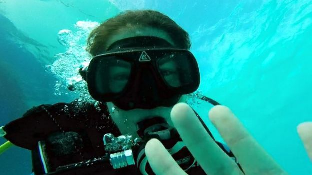A woman underwater in diving goggles waves at the camera