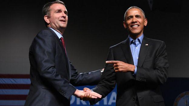 Former US President Barack Obama (R) gestures to Democratic Gubernatorial Candidate Ralph Northam