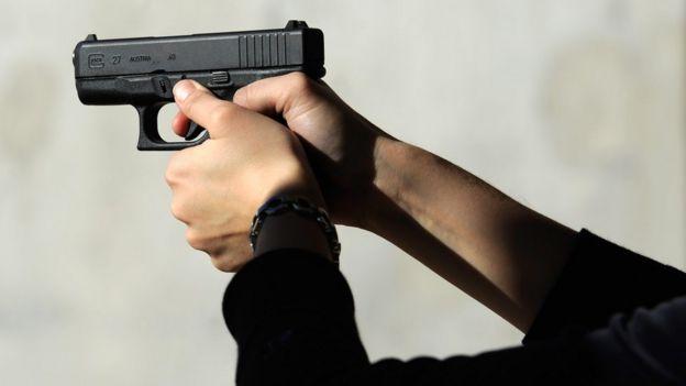 Unas manos de mujer sostienen una pistola de calibre .40