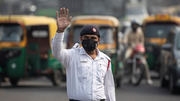 A traffic policeman wears a mask to protect himself from air pollution at a junction during restrictions on private vehicles based on registration plates, on a smoggy morning in New Delhi, India, November 4, 2019.