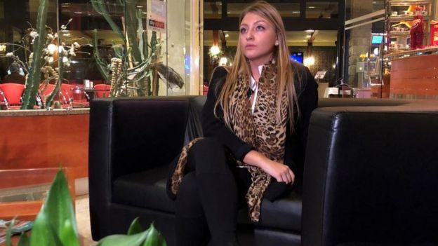 Anna Bolzonaro posa para foto, sentada em uma poltrona