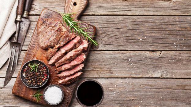 Carne grelhada e fatiada em uma tábua, cercada por potinho de sal, primenta e com um ramo de alecrim ao lado
