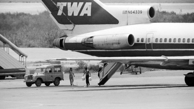 A Lebanese employee at Beirut airport takes bags of sandwiches on board of TWA Flight 847
